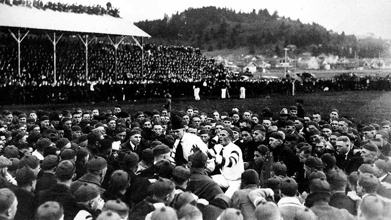 Two UO yell kings in the middle of a throng of students at Hayward Field on November 15, 1919, prior a football game against Oregon Agricultural College.