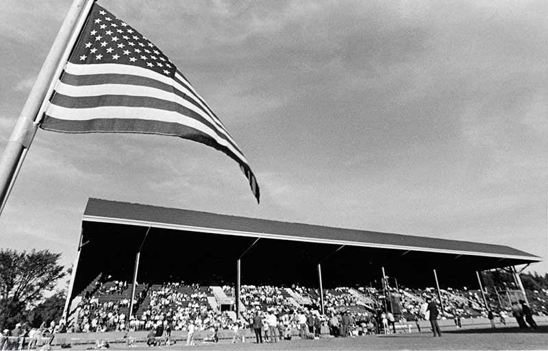 The east grandstand at Hayward Field taken during a late 1960s meet, with an American flag in the foreground at left.