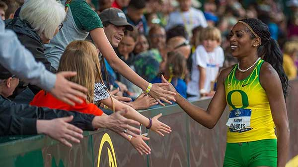 Raevyn Rogers getting high-fives from fans on a victory lap at Hayward Field