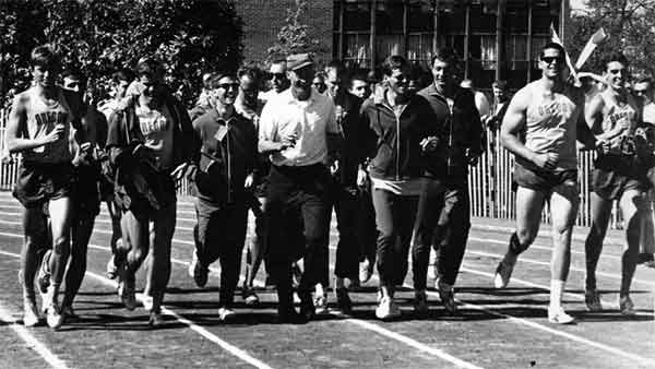 Members of the University of Oregon's 1964 national champion men's track and field team, led by coach Bill Bowerman (near middle wearing hat), as they take a victory lap at Hayward Field