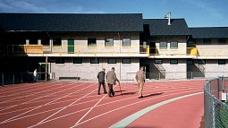 Former track coach Bill Bowerman and two other men walking on the Hayward Field track, away from camera towards the Bowerman Building