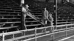 Three men, including University of Oregon athletic director Leo Harris (holding the sledge hammer) posing for a commemorative shot as work to remove the north bleachers at Hayward Field is set to begin in 1950.